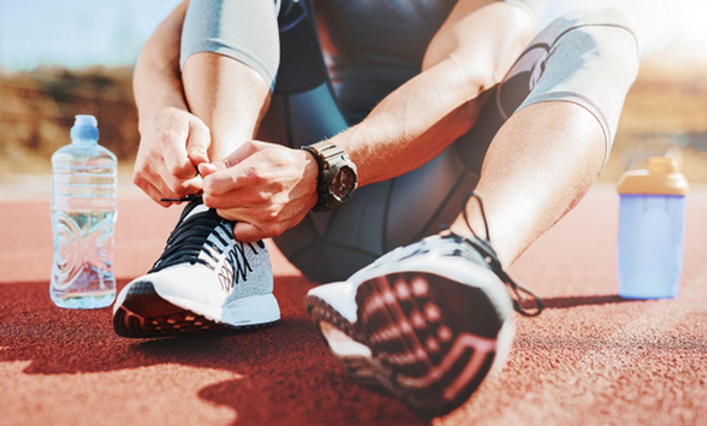 Sportovec sedí na atletické dráze a zavazuje si tkaničku u boty.