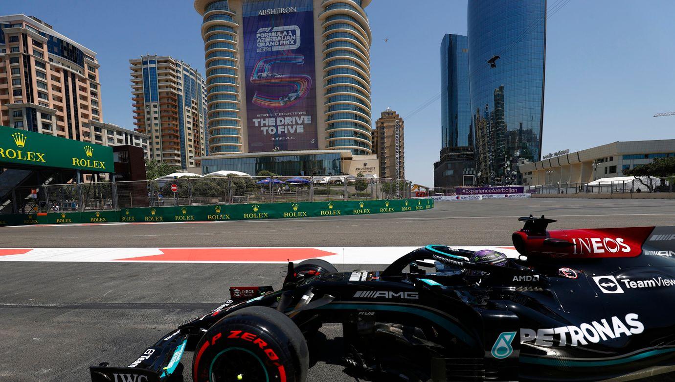 Monopost týmu Mercedes pózuje před výškovými budovami v Baku.