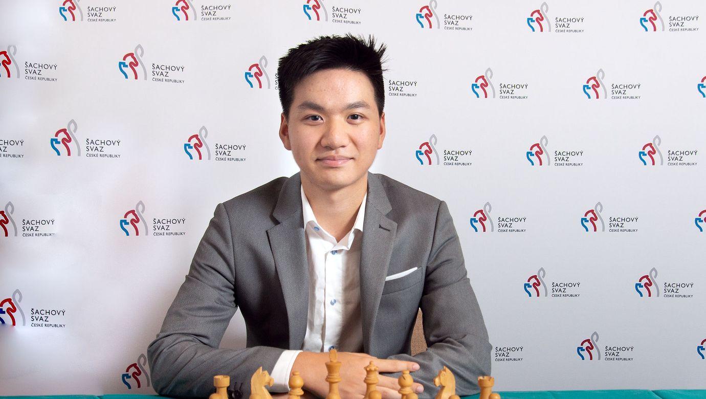 Za šachovnicí sedí v šedém saku šachista Thai Dai Van Nguyen
