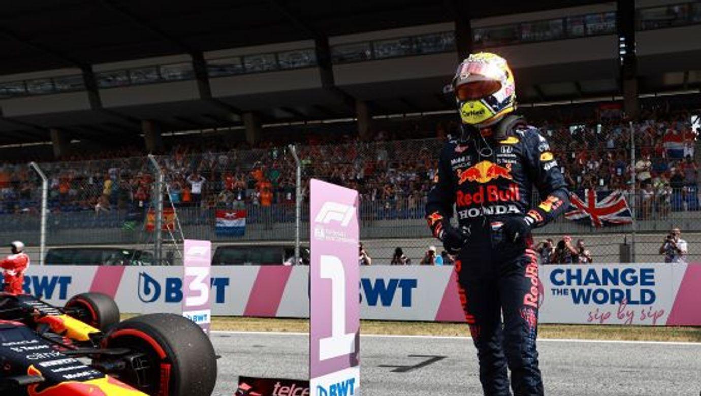 Max Verstappen stojí na trati vedle svého vozu Red Bull.
