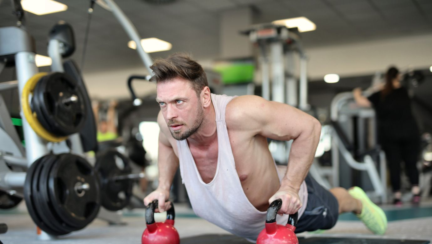 athletic-man-with-fit-muscles-doing-push-ups-on-kettlebells-3837474