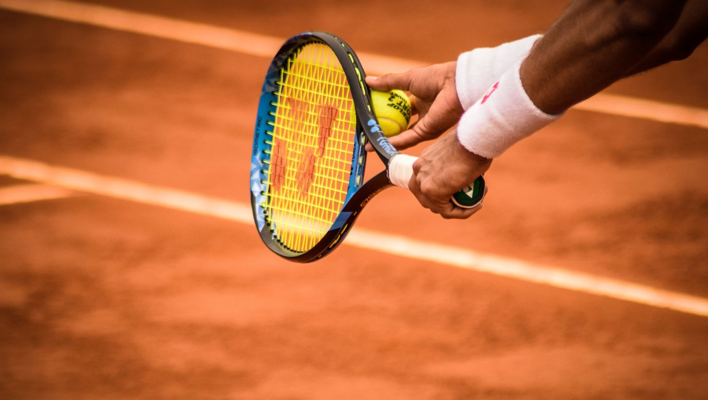 close-up-photo-of-person-holding-tennis-racket-and-ball-1432039