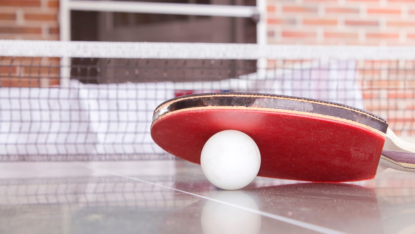 white-pingpong-ball-beneath-red-table-tennis-paddle-187329