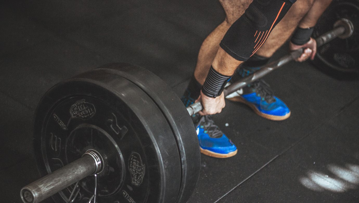 close-up-of-a-person-s-lower-body-holding-barbell-949134