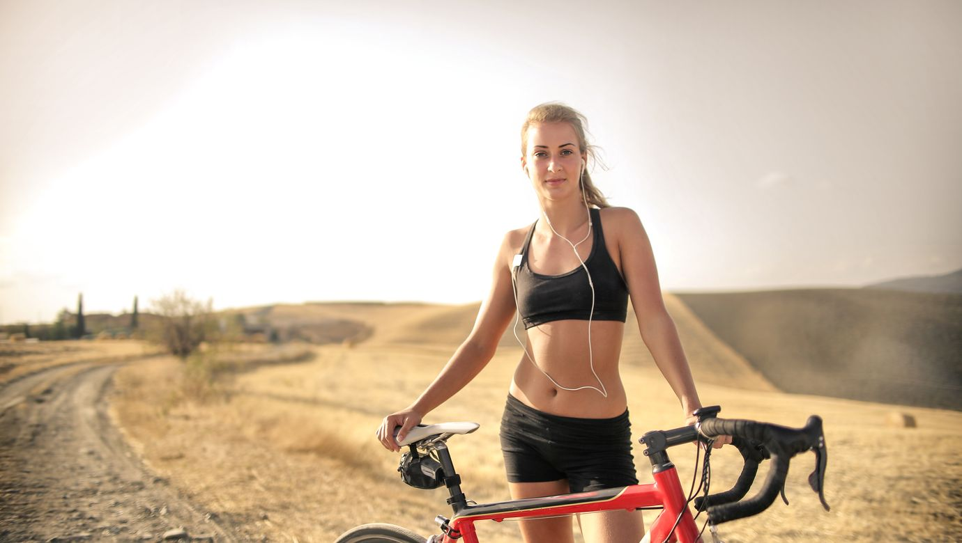confident-athletic-woman-with-bicycle-on-countryside-road-3771805