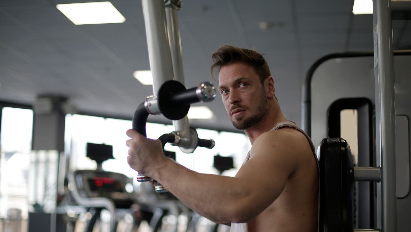 man-in-white-tank-top-holding-exercise-equipment-3888405