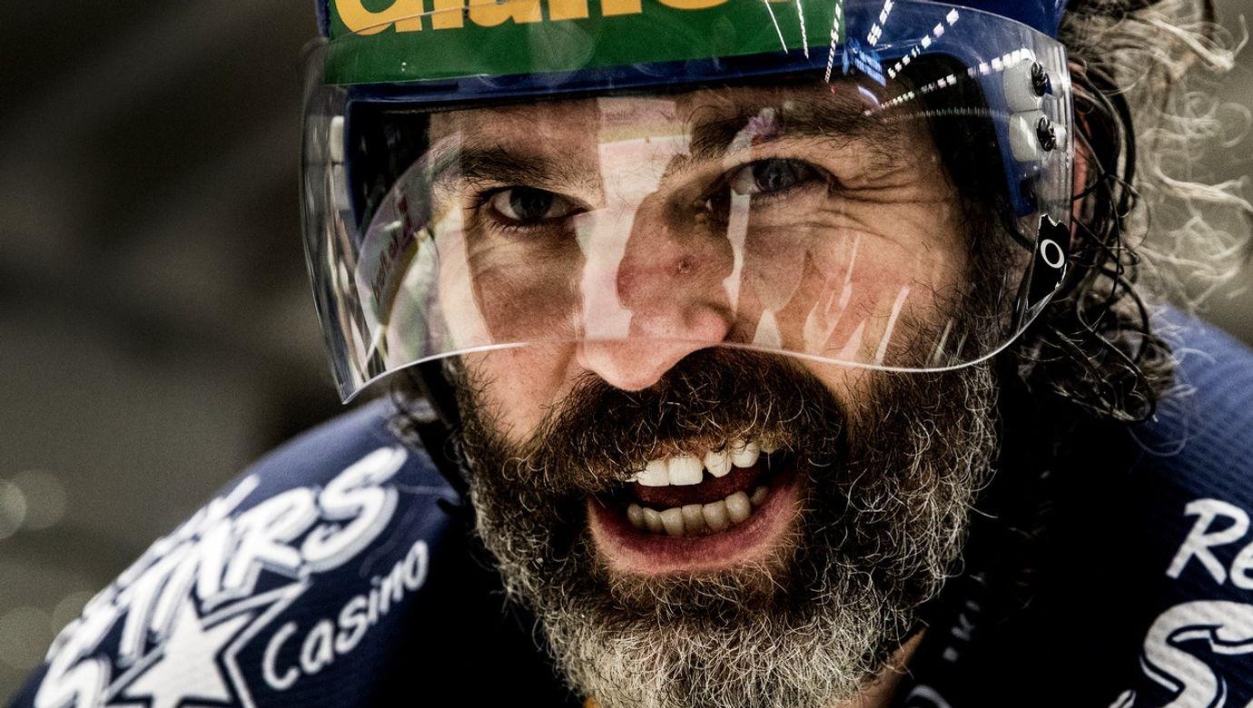Portrét Jaromíra Jágra v hokejové přilbě s plexi štítem.