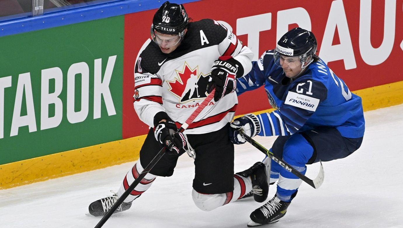 Kanaďan Troy Stecher bojuje o puk s Finem Jere Innalou.