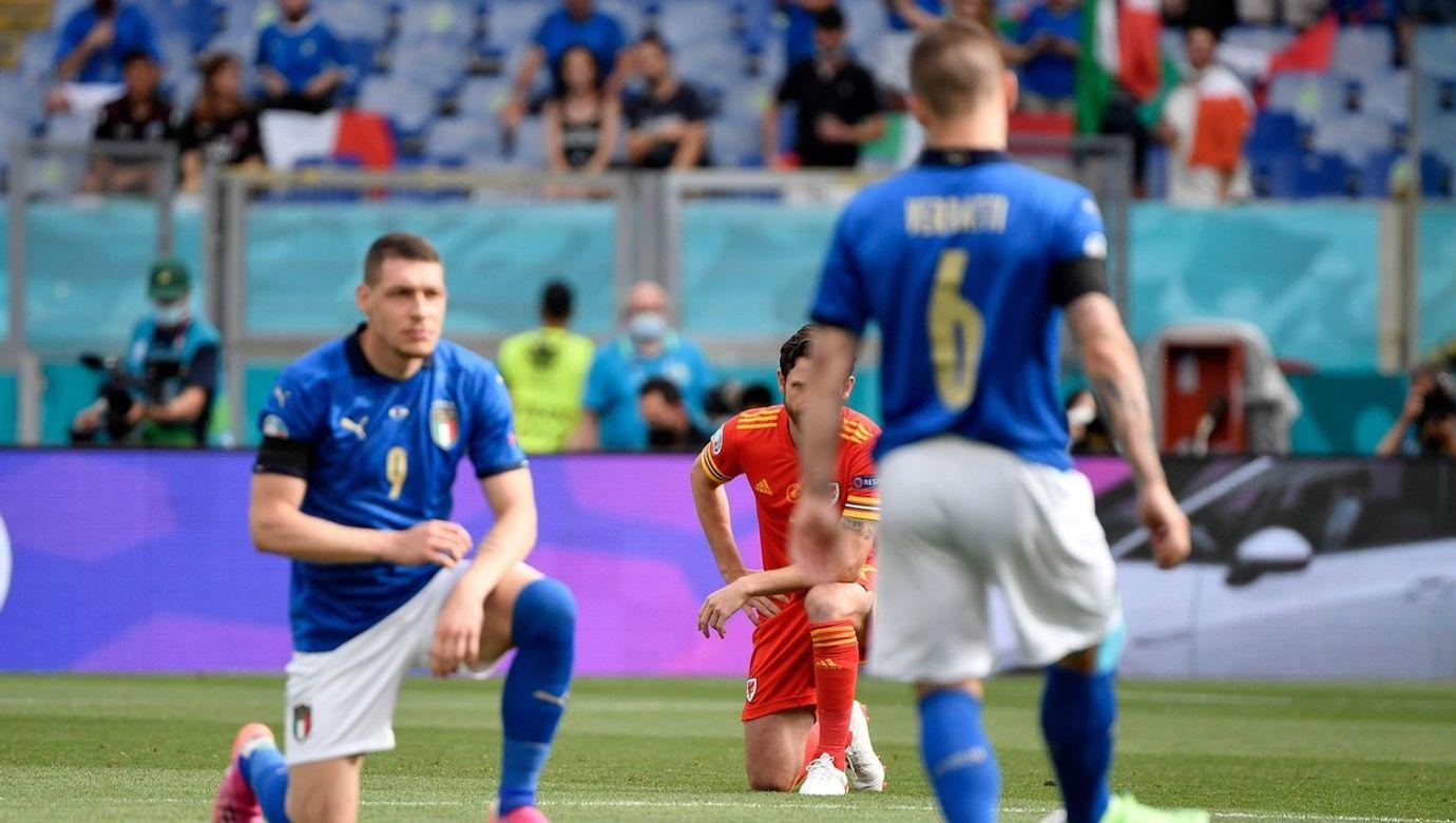 Italský hráč klečí před zahájením utkání, druhý si hraje s míčem.