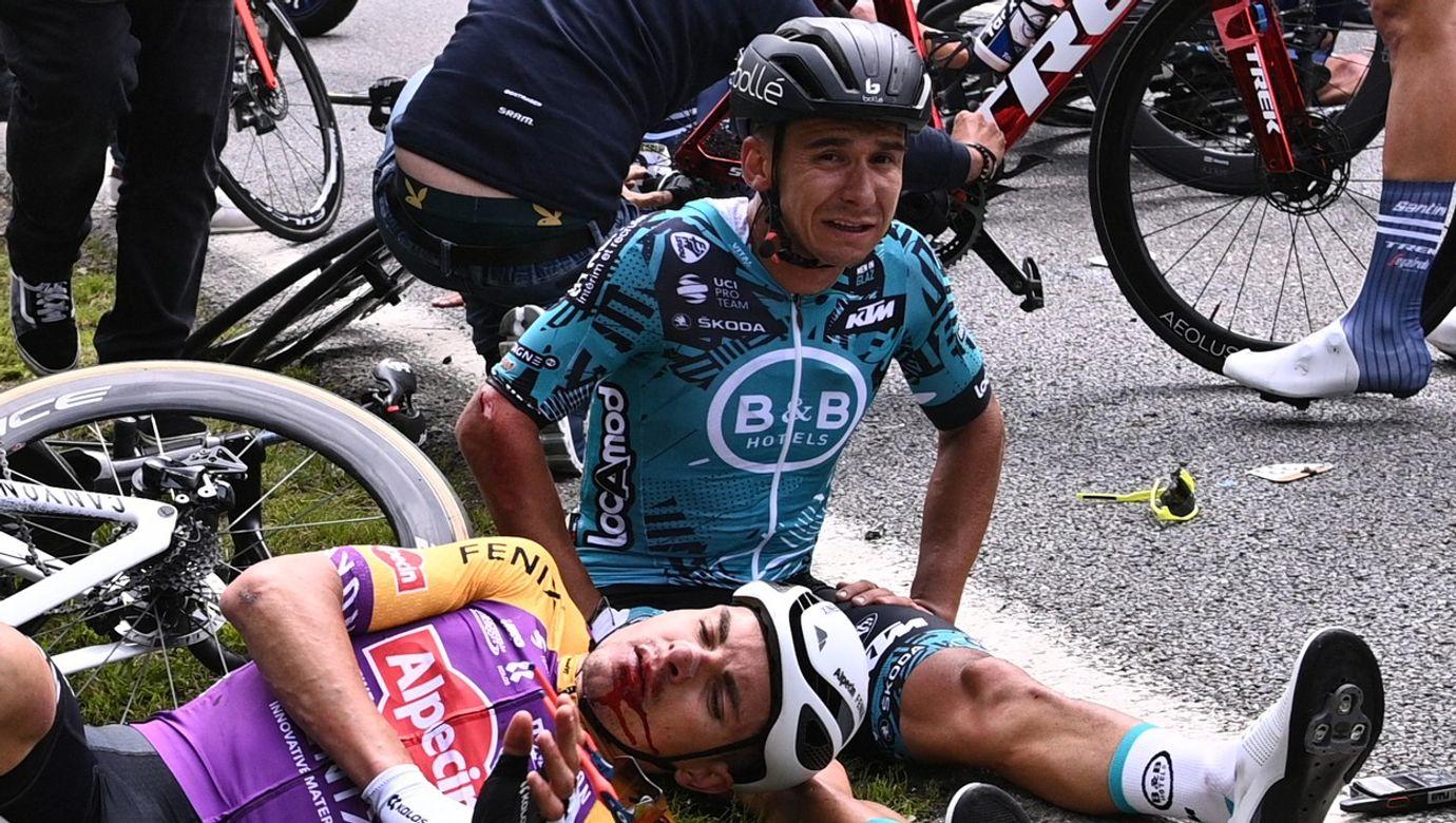 Zranění cyklisté sedí u krajnice a čekají na ošetření.