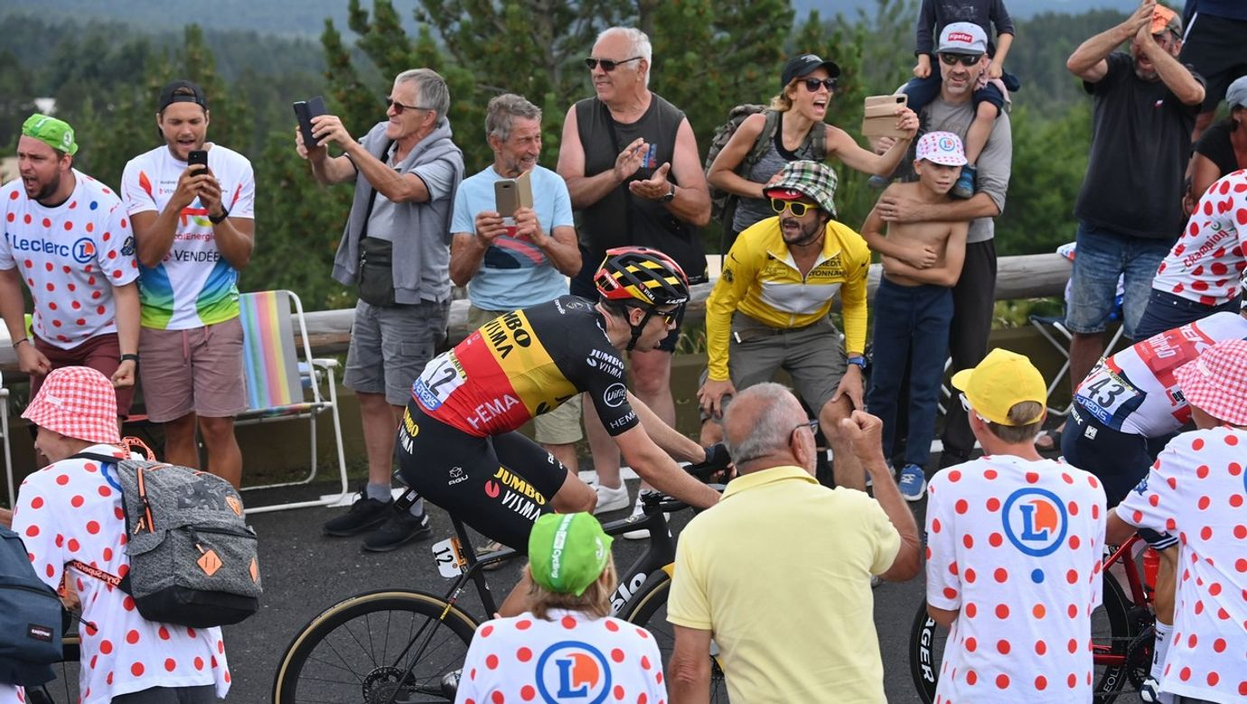 Cyklista Wout van Aert se prodírá ve stoupání mezi fanoušky.