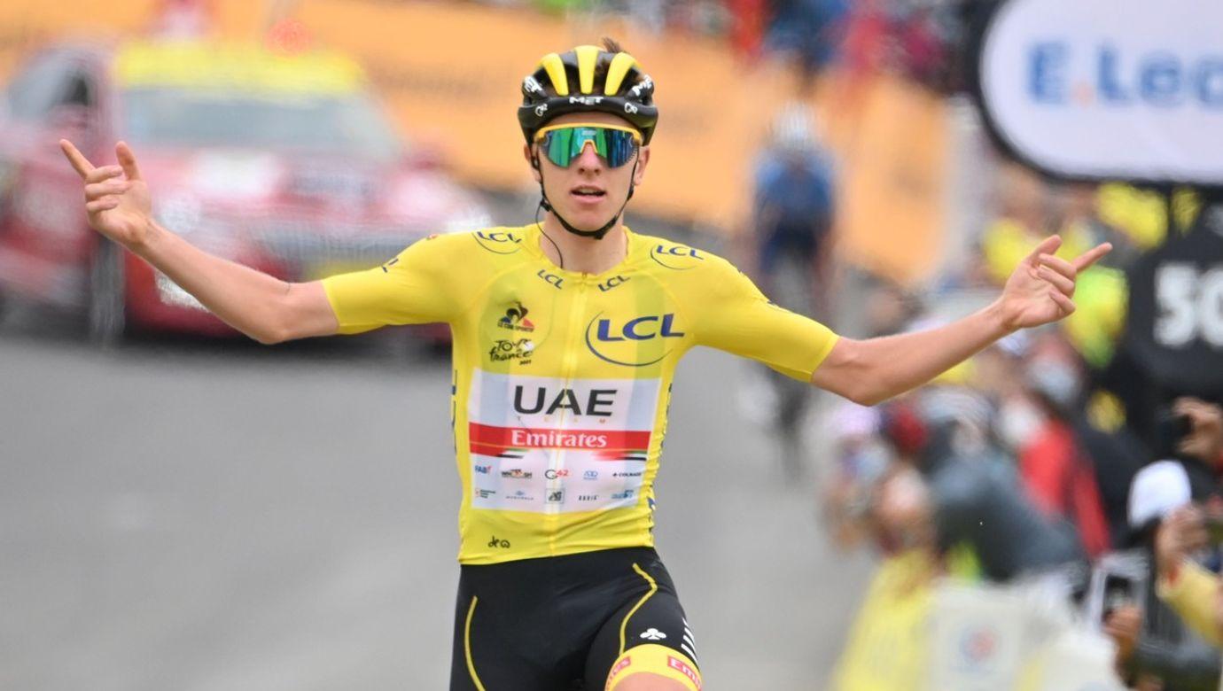 Tadej Pogačar ve žlutém dresu projíždí jako první cílem 18. etapy Tour de France.