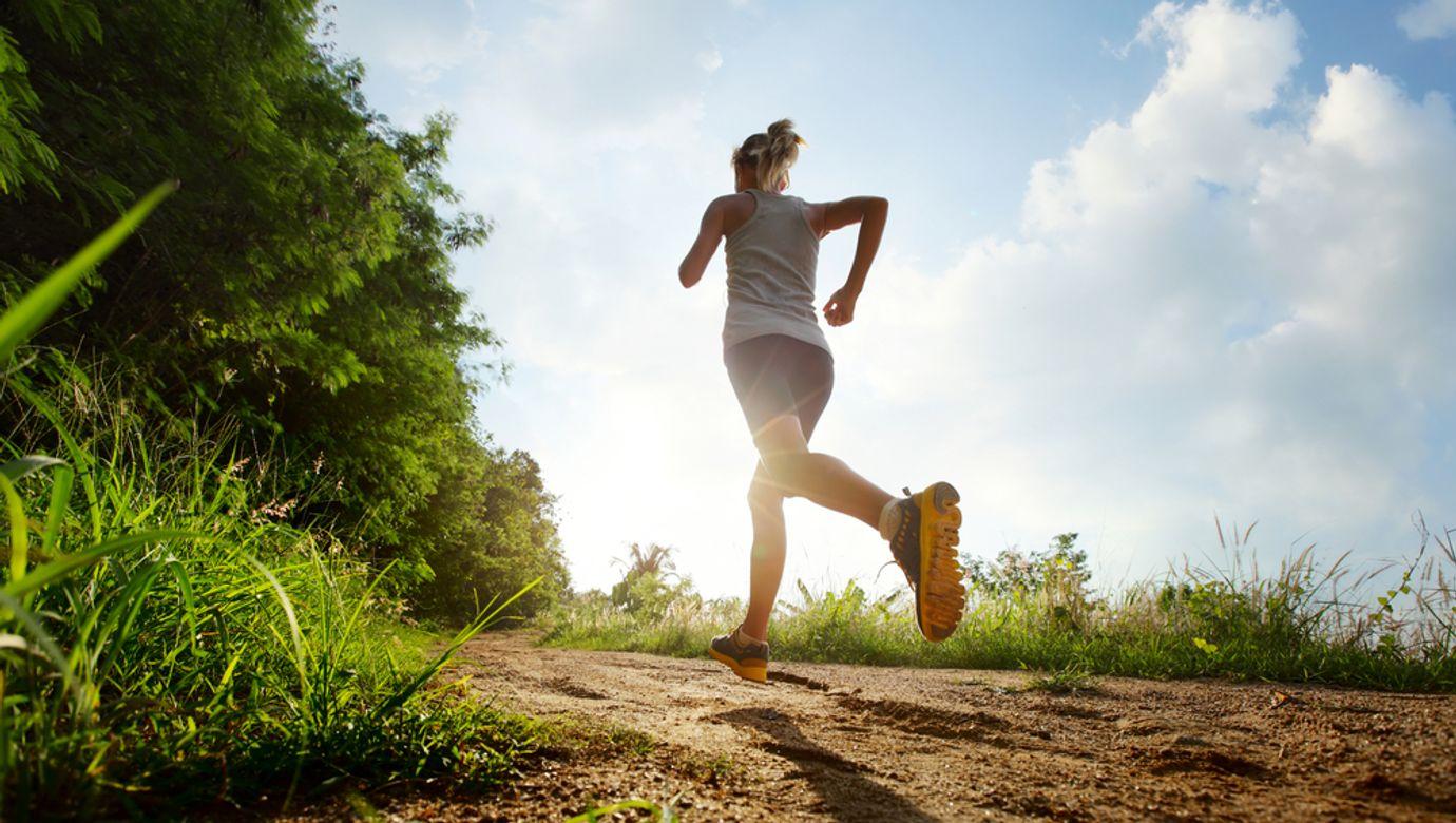 Žena běžící po lesní cestě.