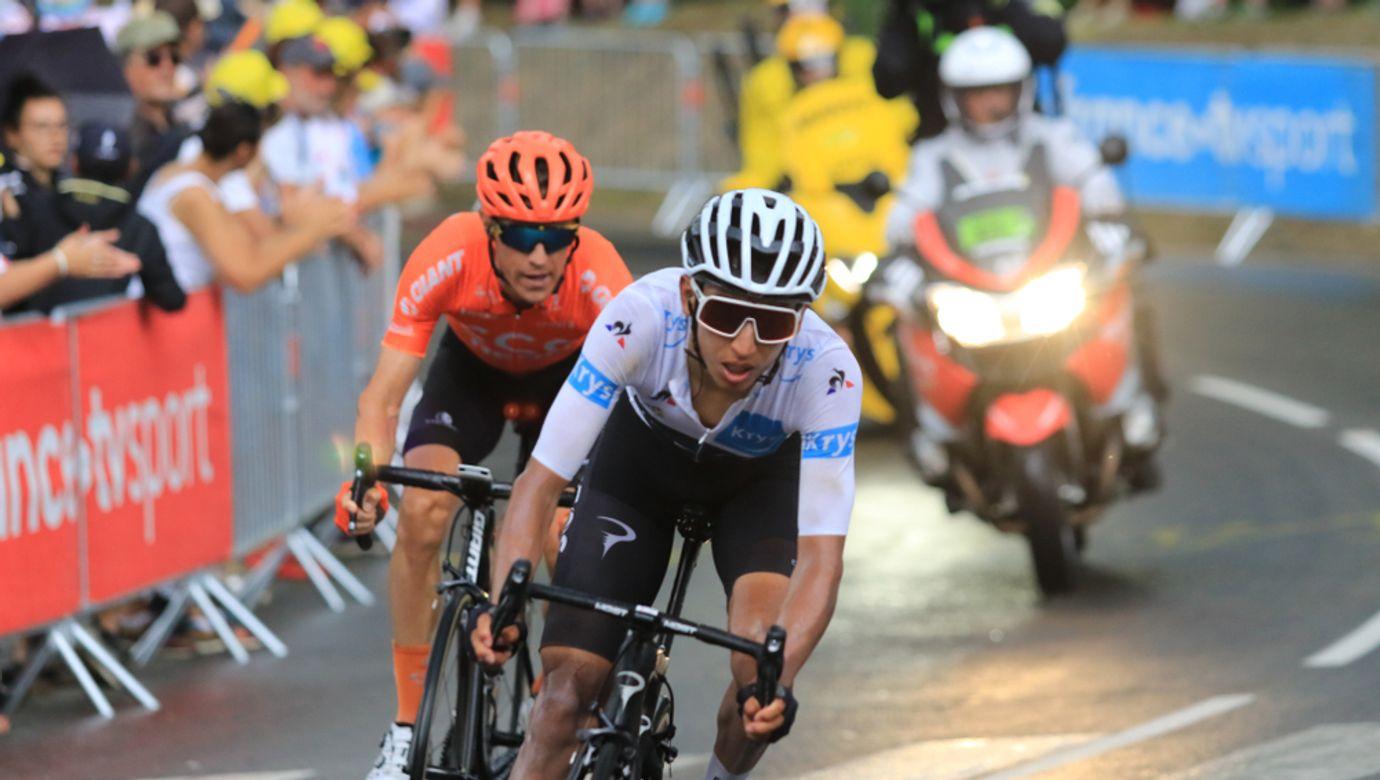 Cyklista Egan Bernal v bílém dresu, za ním soupeř v červeném dresu a doprovodná motorka.