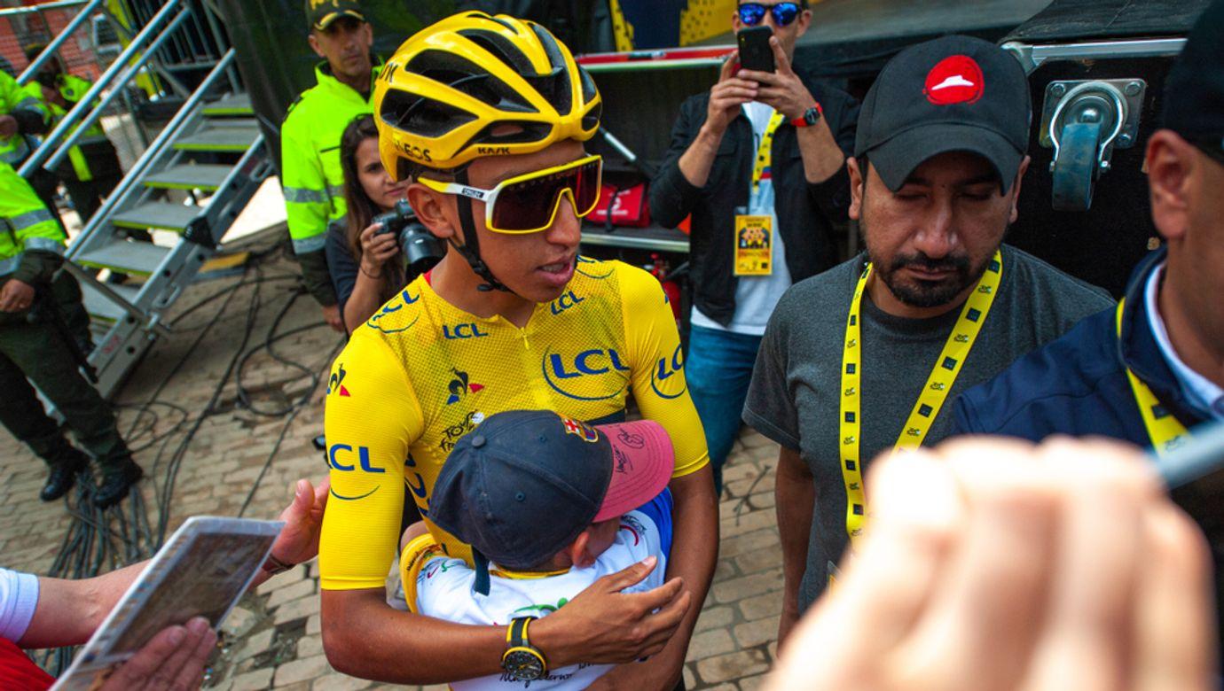 Egan Bernal se věnuje před startem závodu fanouškům, objímá malého chlapce.