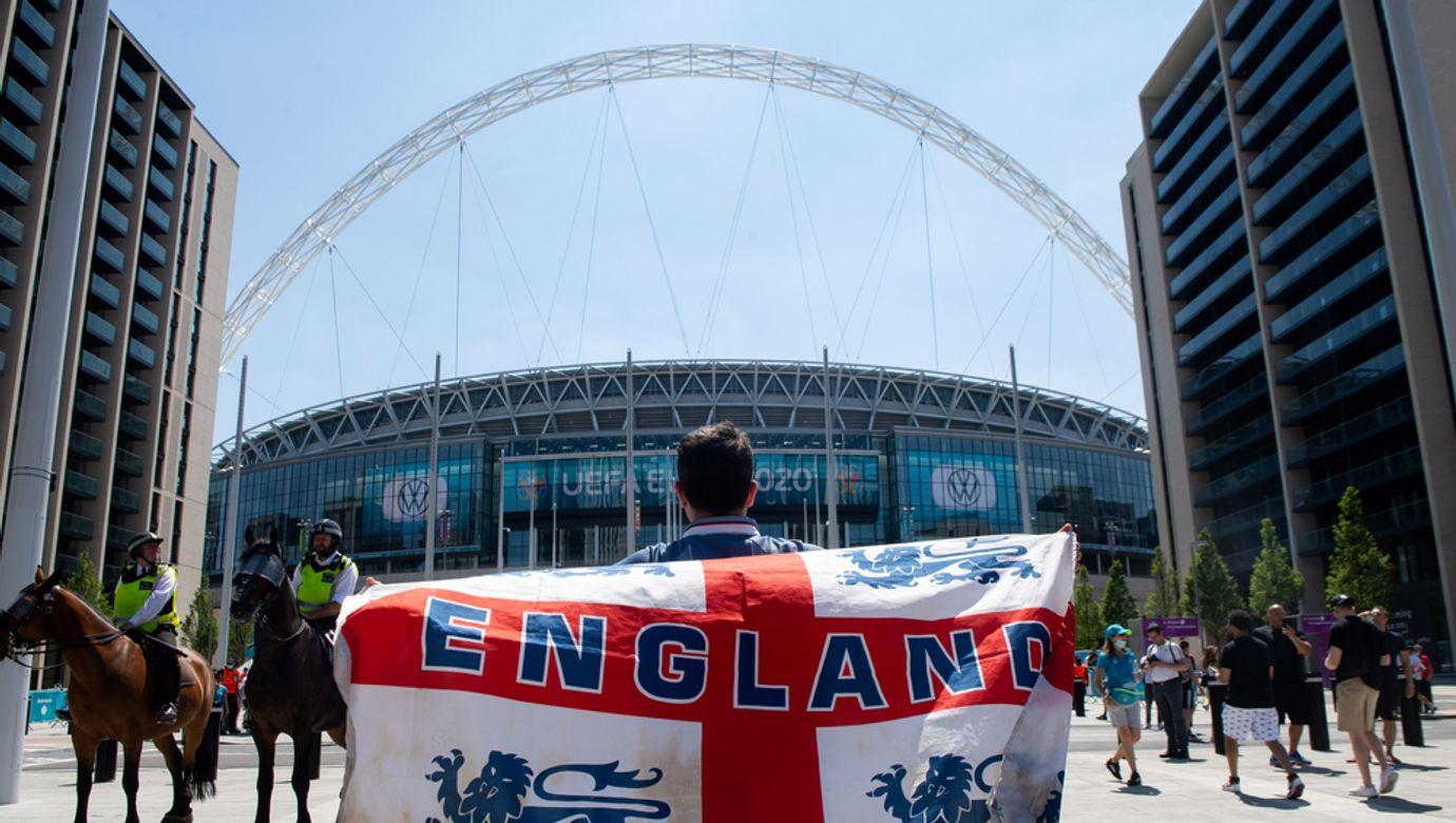 Fanoušek zahalený do anglické vlajky stojí před staionem Wembley.
