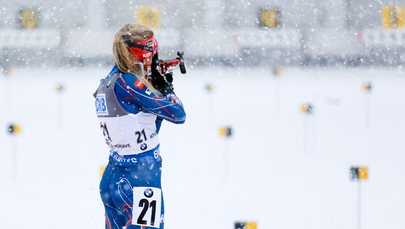 Biatlonistka v modré kombinéze střílí vestoje.