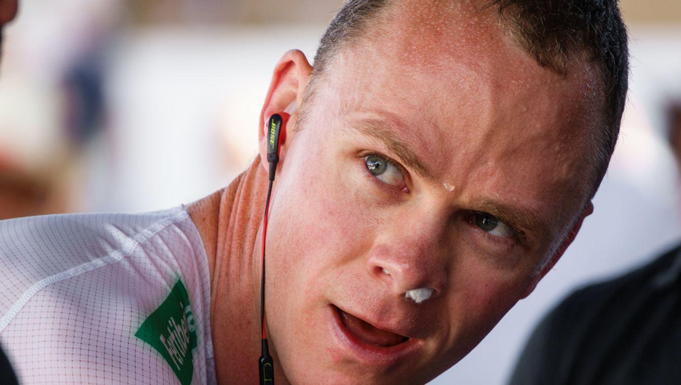 Portrét Chrise Frooma rozjíždějícího se se sluchátky v uších na válcích.